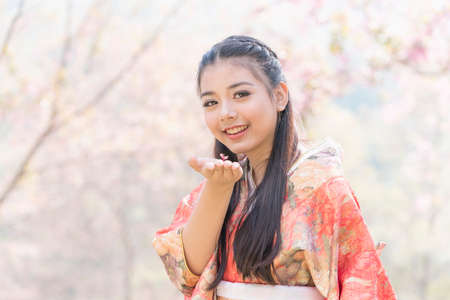 A young woman showing cherry blossoms on her hand under a cherry tree in Japan.