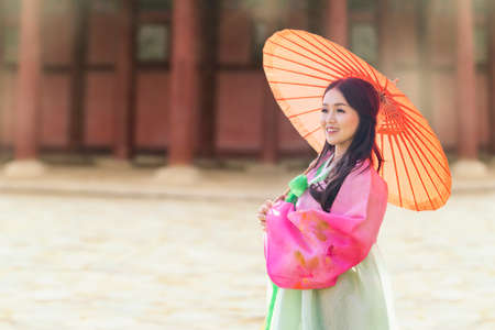 Korean girl wearing a hanbok wearing yellow umbrella. The famous palaces in Seoul. Beautiful Female wearing traditional Korean hanbok in seoul, Korea.