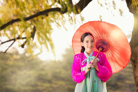 Asian woman tourists. Korean girl wearing a hanbok wearing a umbrella. Beautiful Female wearing traditional Korean hanbok with Large pine in spring, Korea.