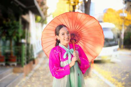 The famous palaces in Seoul. Korean girl wearing a hanbok wearing red umbrella. Beautiful Female wearing traditional Korean hanbok with Ginkgo biloba pine trees in autumn, Seoul, Korea.