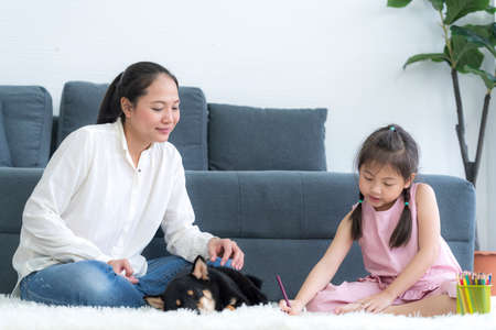 A mom teaches her daughter to do homework in the living room with a Shiba Inu dog.