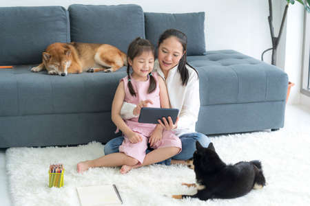 Mom and daughter are having fun using the tablet in a living room with dogs.