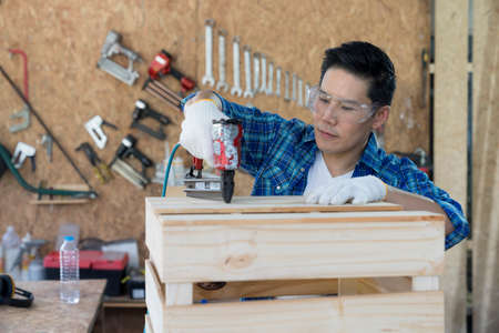 Carpenter hammering nails into wood with a automatic nailer. Process of carpenter worker with machine at wood workshop.