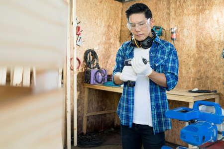 Carpenter Drilling Wood. Carpenter making wooden furniture in workshop.