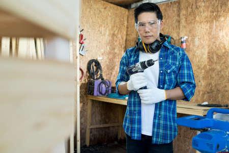 Carpenter Drilling Wood. Young carpenter man in hardhat drilling wood in working studio.