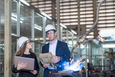 Work in a Heavy Industry Manufacturing Factory. Industrial man and woman engineer with laptop in control robot of factory. Stockfoto