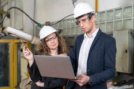 Engineering technology and industry. Man and woman talking and using laptop computer with robot arm production line. Stockfoto