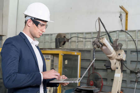 The engineer is explaining the operation of the machine. Man using laptop computer with robot arm production line.