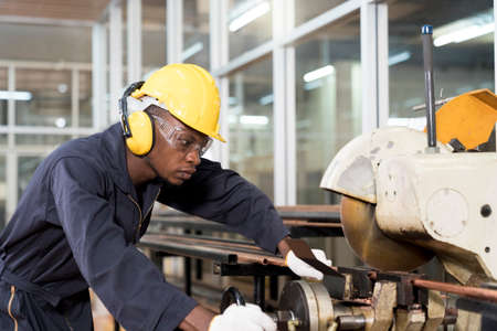 The factory mechanic is using a saw to cut the copper pipe. An expert technician is inspecting industrial machinery in a steel factory. Stockfoto