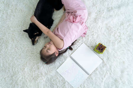An Asian girl is sleeping hugging a Shiba Inu on the carpet in the living room.