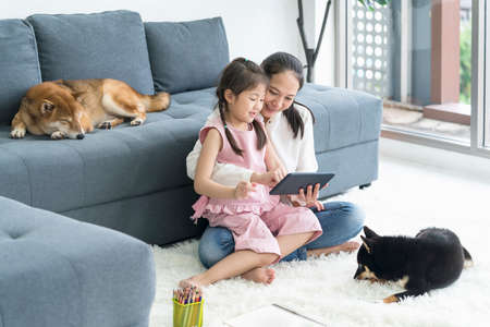 An Asian girl with her mother is using a tablet. In the living room with a black Shiba Inu