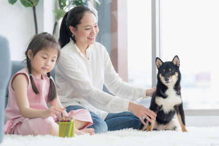 An Asian girl with her mother is in a living room with a black Shiba Inu. Morning sunshine with mom and baby and her dog