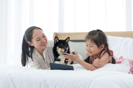 An Asian girl with her mother sits on a bed with a Shiba Inu. A girl hands together for success with a dog. Stockfoto