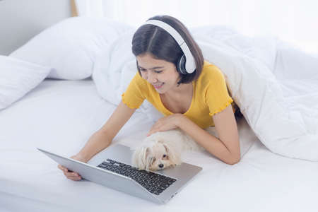 An Asian girl watching a movie, listening to music on her laptop, in bed with a maltese.