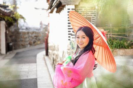 Korean girl wearing a hanbok wearing umbrella. The famous palaces in Seoul. Beautiful Female wearing traditional Korean hanbok in spring, Old town Seoul, Korea.