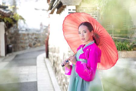 Korean girl wearing a hanbok wearing Pink umbrella. The famous palaces in Seoul. Beautiful Female wearing traditional Korean hanbok in spring, Old town Seoul, Korea.