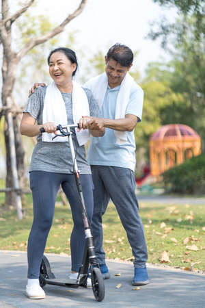 An elderly couple is teaching his wife to play a scooter. Sporty mature couple staying fit with sport. Archivio Fotografico