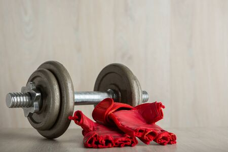 Iron dumbbell and fitness glove on a wooden floor