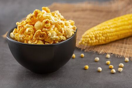 Popcorn in the black bowl and raw corn on the black table 版權商用圖片