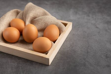 Chicken eggs on the wooden tray on the black table. High angle view. 版權商用圖片