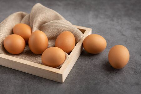Chicken eggs on the wooden tray on the black cement floor. High angle view.