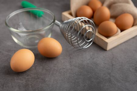 Chicken eggs on the wooden tray, egg beater and glass bowl on the black cement floor. High angle view.