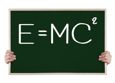e=mc² on blackboard with hands photo