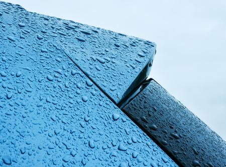 retained: Las gotas de lluvia retenidos en azul pintura metálica de un coche.