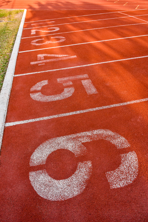 numbering: Running track start line with lane numbering 1 to 6 paving surface