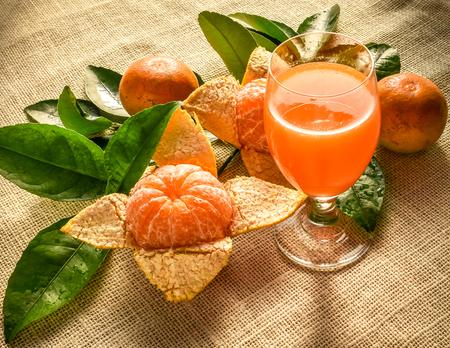 Glass of orange juice and fruits on burlap background,back light shot. Healthy eating lifestyle.