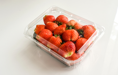 Strawberry in plastic packaging, white background. Distilled water drops seen under the package cover.