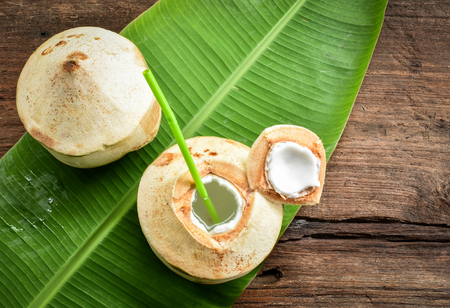 Two fresh coconut fruits ready to serve as beverage. Young coconut fruit cut open to drink sweet  juice and eat. Flat lay on green banana leaf and wood background.