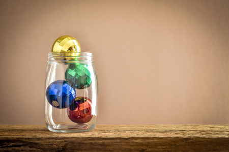 Colorful season greetings decoration balls in glass jar with classic tone wall background. Business concept about funds and investment.Copy space provided.