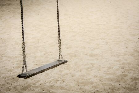 Rope swing on beach playground under shade. Swing under a tree by the beach.