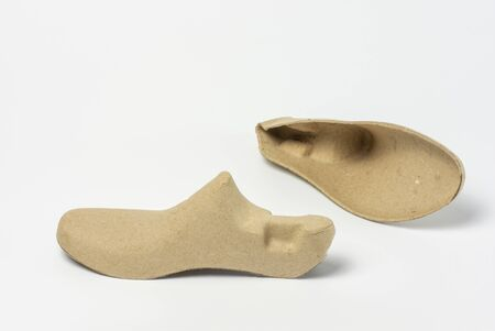 Pair of shoe trees made of recycled paper on white background.