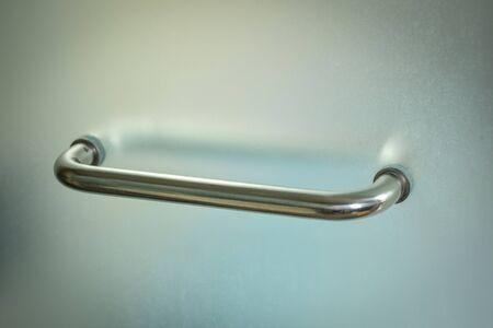 Glass door handle of a glass partition shower unit. Bathroom glass door detail with selective focus