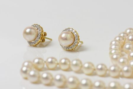 Pair of natural pearl earrings on white with pearl necklace in the background.