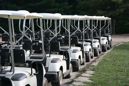 A row of golf carts waiting for golfers at a country club. Green grass to the right and room for copy space.