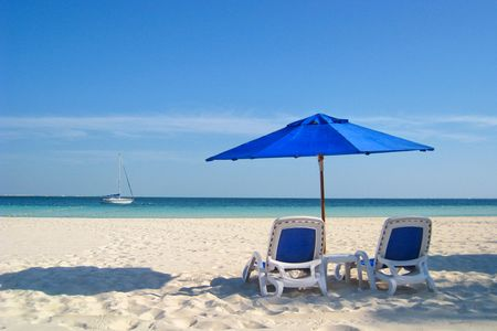 Two beach chairs under a blue umbrella on the white sandy beach at a resort.