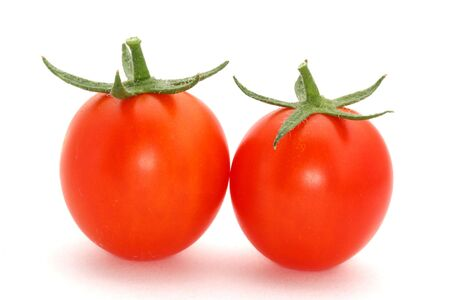 close up of two cherry tomatoes in a row on a white background