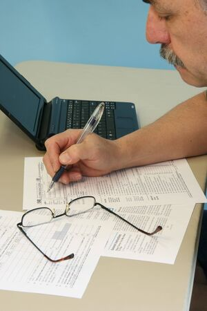 Man Filling in 1040 Federal Income Tax Form photo