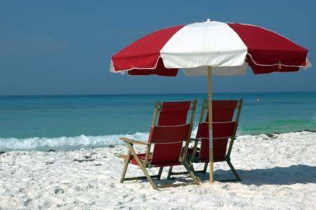 ombrellone spiaggia: due sedie e ombrellone sulla spiaggia di sabbia bianca