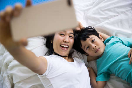 close up of happy mother and her son Taking pictures or selfie or video call or relatives in a bed. Concept of new generation, family, parenthood, authenticity, connection