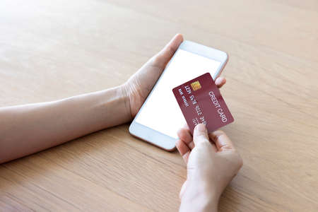 A woman shopping online on her table at home with a smartphone using a red credit card. And use your credit card to tap the screen to verify the identity. Concept about business. over shoulder shot.