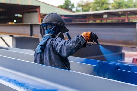 The painter is working to painting color top coat on steel structure with spray gun, at industrial factory.