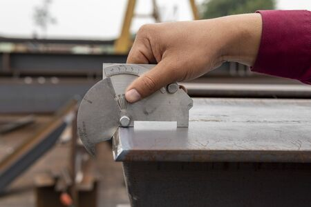 Using the welding gauge to measure the angle of edge h-beam after cutting. Banque d'images