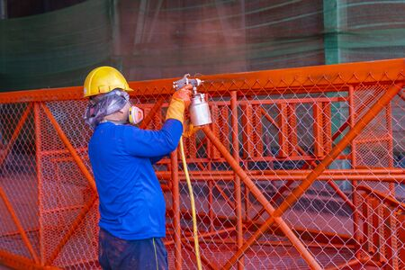 The painter is working to painting the steel structure with spray gun, at industrial factory.