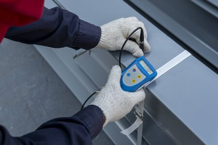 Measure dry film thickness (DFT) with Coating Thickness Gauge for painting on steel structure, at industrial factory.