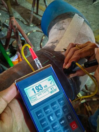 Hardness testing of alloy pipe and welding after a post weld heat treatment (PWHT), Focus on monitor Stock Photo
