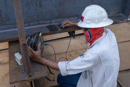 The inspectors are checking defect in welded of steel add joint with process Ultrasonic testing (UT) of Non-Destructive Testing(NDT) at industrial factory.